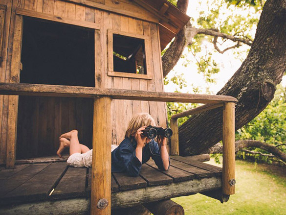 Kid in treehouse using binoculars PP stock photo